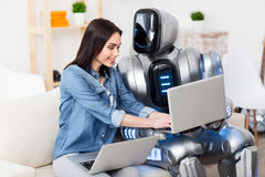 Positive girl and robot sitting on the couch Royalty Free Stock Photos