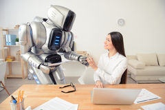 Positive girl and robot working in the office Royalty Free Stock Photos