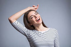 Positive girl smiling  isolated on grey background. Joyful moment.  Positive content beautiful girl smiling and holding her hand on the head  while standing Royalty Free Stock Image