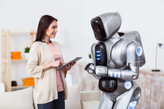 Positive girl standing with the robot. Modern world. Pleasant beautiful delighted girl using tablet and expressing gladness while standing with robot stock image