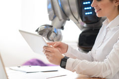 Positive girl using tablet with robot Stock Photography