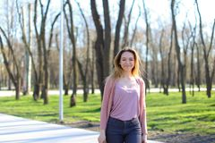 Positive girl walking in park and smiling. Positive girl walking in park and having cute smile. Concept of spring weather and open air stock image