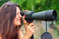 Positive girl watching in spotting scope. Stock Photo