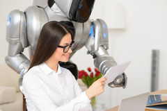 Positive girl working in the office with robot Royalty Free Stock Image