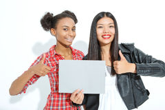 Positive girls holding sheet of paper Royalty Free Stock Images