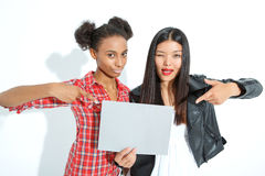 Positive girls holding sheet of paper Royalty Free Stock Photography