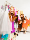 Positive girls during shopping behind hangers Stock Photo