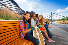 Positive girls with skateboards sit on long bench Royalty Free Stock Image