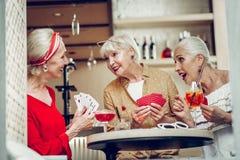 Positive glückliche Spielkartespiele der Freundinnen stockfotos