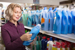 Positive glad female with selecting fabric conditioner Royalty Free Stock Images