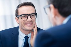 Positive glad man checking his look Royalty Free Stock Images