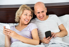 Positive glad mature couple together social networking Stock Image