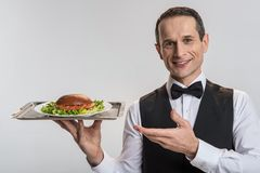 Positive good looking male waiter bringing order. At your service. Gay optimistic male waiter pointing at tray while staring at the camera and grinning Stock Image