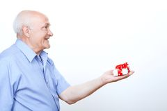 Positive grandfather holding the present Royalty Free Stock Photos