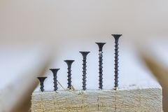 Positive graph made of screws as bar charts on board background Royalty Free Stock Photography