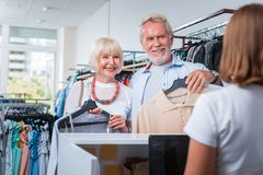 Positive grey haired customers being ready for payment process. Full of gratitude. Positive grey haired customers being pleased while bringing chosen clothes to royalty free stock photos