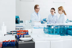 Positive group of scientists being high spirited. Delighted workers. Friendly looking collective wearing protective glasses talking to each other while having Royalty Free Stock Images