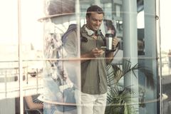 Positive guy is holding mobile phone with smile Stock Photography