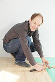 Positive guy installing flooring Stock Images