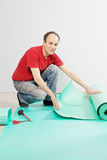 Positive guy with mat. Positive guy in red shirt with sub-flooring mat Stock Photography