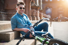 Positive guy relaxing on the footsteps. Full of joy. Cheerful content smiling guy leaning on the footsteps near his bicycle and resting while expressing gladness stock image