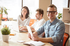 Positive guy sitting at the table in office Stock Images