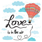 Positive hand drawn slogan Love is in the air decorated hot balloon, hearts, sky, clouds. Positive hand drawn  slogan Love is in the air decorated hot air Stock Image