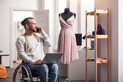 Positive handicapped man discussing details with his colleague Royalty Free Stock Photography