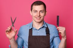 Positive handsome brunett barber shows scissors and comb, dressed in blue shirt and brown apron, ready to do hairstyle for men,. Poses smoling against pink stock photo