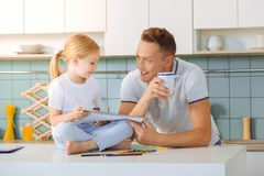 Positive handsome man asking his daughter about the hometask Stock Images