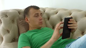 Joyful man websurfing with tablet pc on the couch stock video