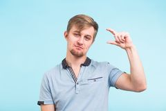 Positive handsome man shows something very tiny or small over blue background. Young fashionable male gestures.  royalty free stock images