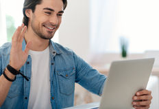 Positive handsome man using tablet. Nice to see you. Cheerful delighted smiling man using tablet and talking through the Internet while expressing gladness royalty free stock photography