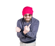 Positive handsome young bearded hipster in pink knitted hat, expresses various emotions and shows different signs the Stock Images