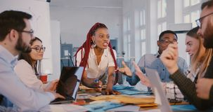 Positive happy black business woman working together with diverse colleagues in modern trendy office, healthy workplace.
