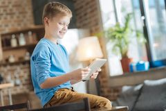 Positive happy boy looking at the tablet screen Royalty Free Stock Photos