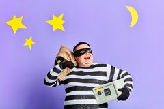 Positive happy burglar has stolen money from safe. Happu man looking up, enjoying good day for crime stock images