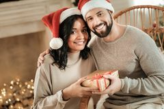 Positive happy couple holding a gift box stock images