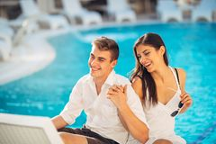 Positive happy couple relaxing by the swimming pool in luxury summer vacation resort.Enjoying time together in spa wellness center stock image
