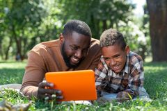Positive happy father and son looking at the tablet screen. Digital device. Positive happy father and son looking at the tablet screen while lying on the grass stock photo