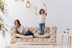 Positive happy girl jumping on the sofa. Pleasurable activity. Positive happy cute girl standing on the sofa and jumping while enjoying herself Royalty Free Stock Image