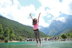 Positive happy life, careless Asian Chinese woman jump by a lake. Asian Chinese woman yoga by a lake, Yulong snow capped mountains on the background, beautiful Stock Photos