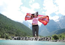Positive happy life, careless Asian Chinese woman jump by a lake. Asian Chinese woman yoga by a lake, Yulong snow capped mountains on the background, beautiful Royalty Free Stock Photography