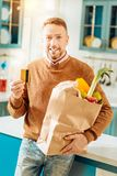 Positive happy man buying food online. Online payment. Positive nice happy man smiling and holding his credit card while buying food online Stock Images
