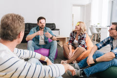 Positive happy people guessing words. Who am I. Positive cheerful nice people sitting in the circle and having sticky notes on their foreheads while playing a Royalty Free Stock Photo