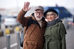 Positive happy senior couple is expressing gladness. Hello. Waist up portrait of cheerful aged men and women are standing together outdoors and hugging while royalty free stock photography