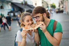 Happy students eating pizza on street. Positive happy students eating pizza on street Royalty Free Stock Image