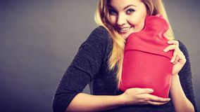 Woman hugs hot water bottle in red fleece cover. Positive happy woman hugging warm hot water bottle in red soft fleece cover, on grey. Health care, pain Royalty Free Stock Photography