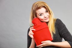 Woman hugs hot water bottle in red fleece cover. Positive happy woman hugging warm hot water bottle in red soft fleece cover, on grey. Health care, pain Royalty Free Stock Image