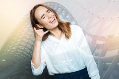 Positive happy woman pretending to make a call. Call gesture. Positive happy delighted woman making a call gesture and smiling while pretending to make a call Stock Photography